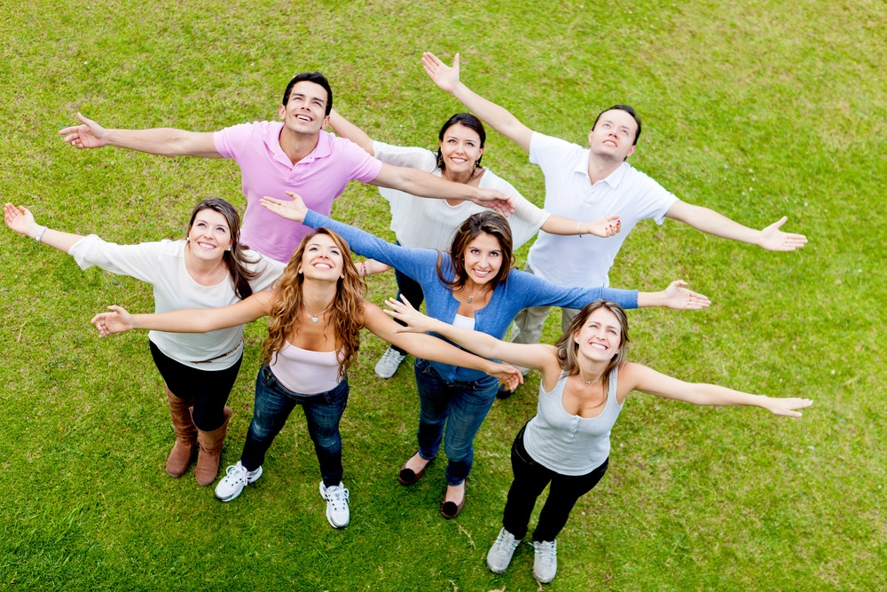 Group of people with open arms outdoors looking up