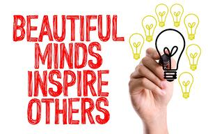 Hand with marker writing the word Beautiful Minds Inspire Others
