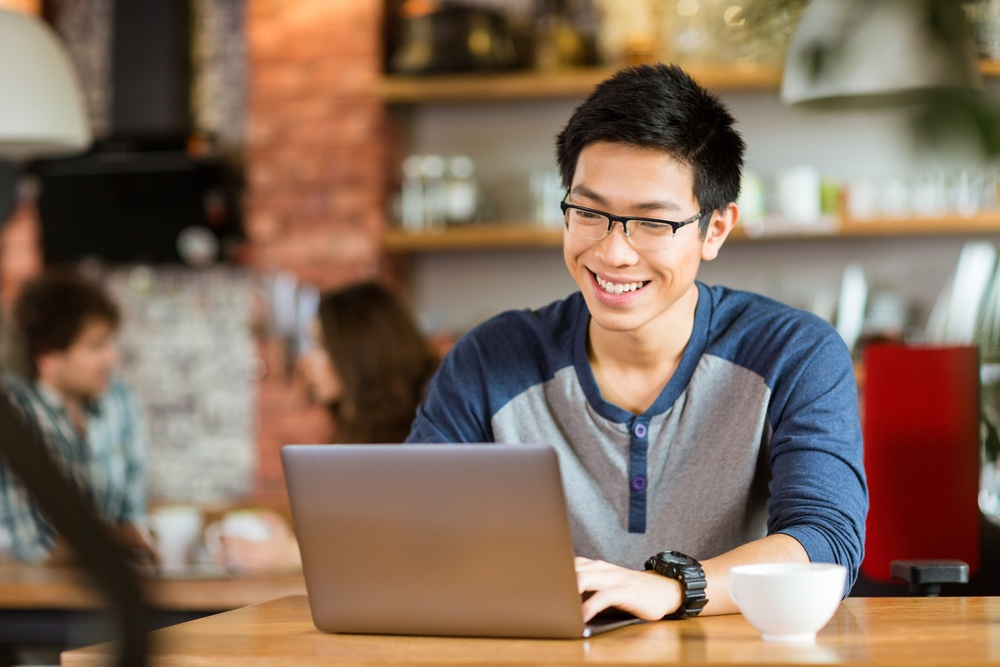 Happy cheerful young asian male in glasses smiling and using laptop in cafe.jpeg