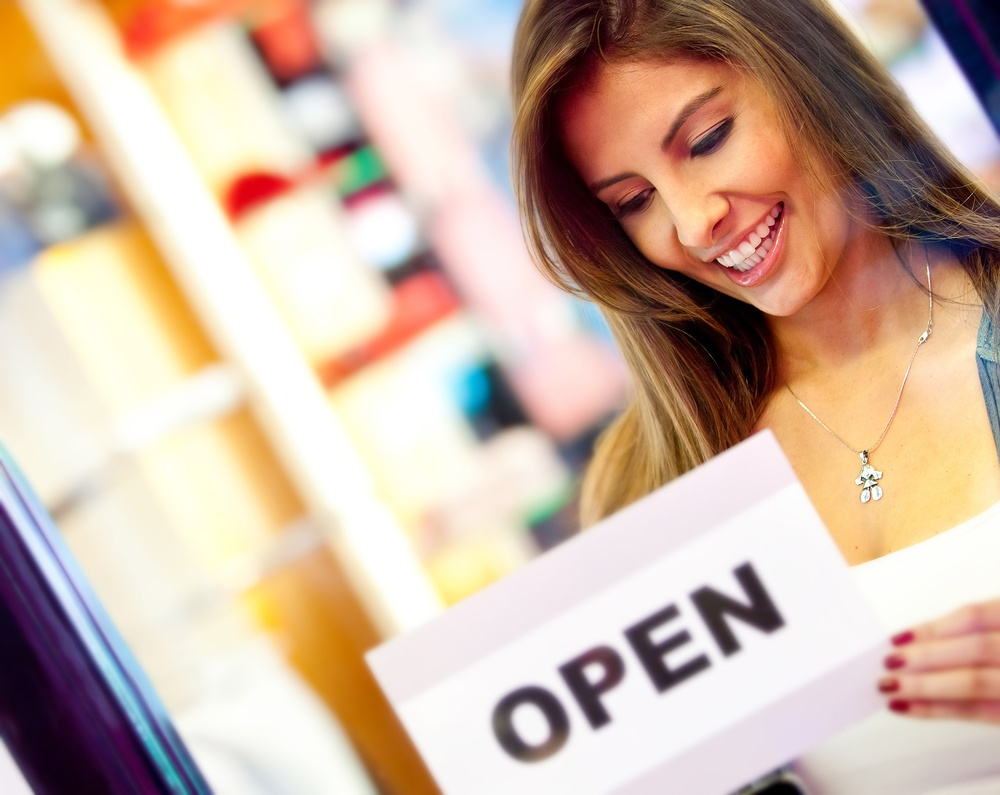 "Woman putting an ""open"" sign at the door of a business store-1"