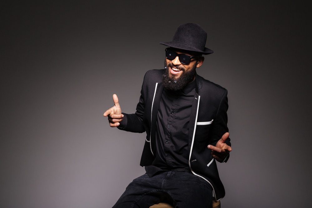 Cheerful afro american man in stylish cloth and glasses posing over black background.jpeg