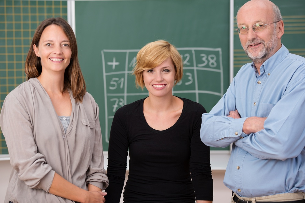 Group of three school teachers with confident friendly smiles standing in front of a class blackboard, one man and two women.jpeg