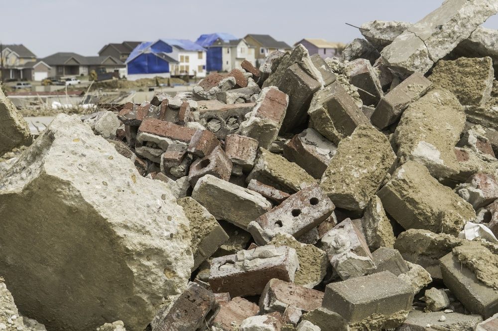 Rubble from destroyed homes remains heaped up in neighborhood where other houses undergo repair during recovery more than 4 months after a tornado in Washington, Illinois, USA.jpeg