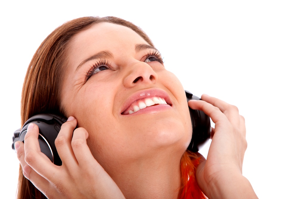 girl listening to music looking happy isolated over white.jpeg